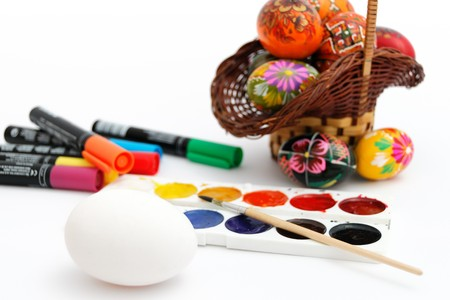 White egg against a basket with painted eggs, paints, markers