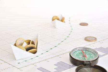 Papieren schepen carring munten langs groeiende financiële diagram Stockfoto