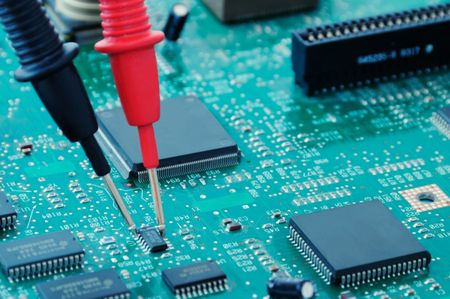 A circuit board with microchips and multimeter probes Stock Photo