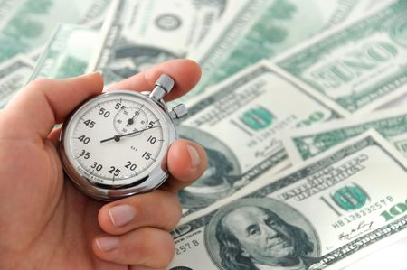 Menselijke hand houden van een stop-watch tegen dollar bank nota Stockfoto
