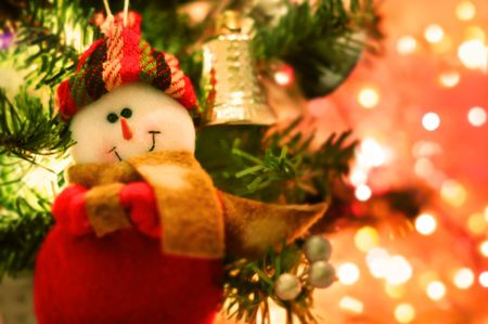 Smiling snow man Christmas tree decoration hanging on the spruce Stock Photo