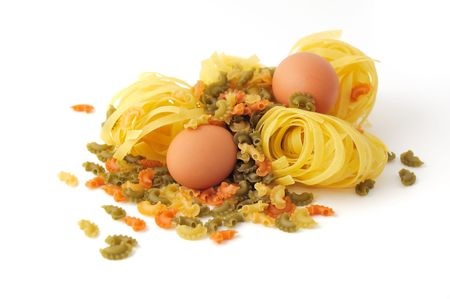 Food ingredients: uncooked spaghetti and eggs isolated on white background.