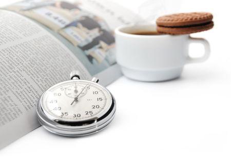 Stopwatch op de achtergrond van een krant en een kopje koffie met biscuit � korte pauze van een zakenman Stockfoto