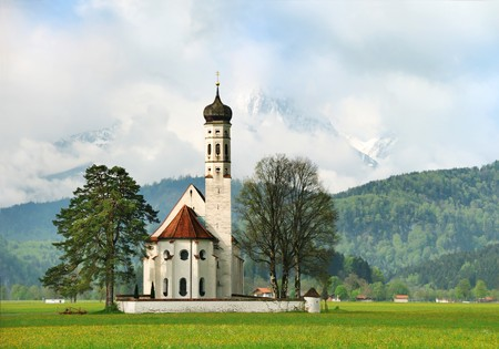 Little church in the countryside with Alps on the background early in the morning Stock Photo