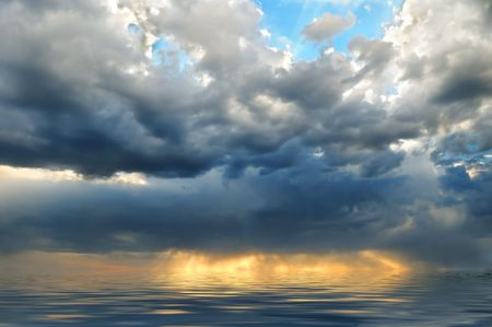 Bright evening sky with storm clouds and sunbeams reflecting in the sea photo