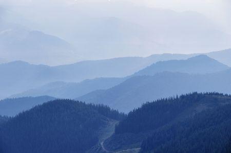tonalit�: Silhouettes de montagnes anciennes au cours du matin brumeux en tonalit� bleue