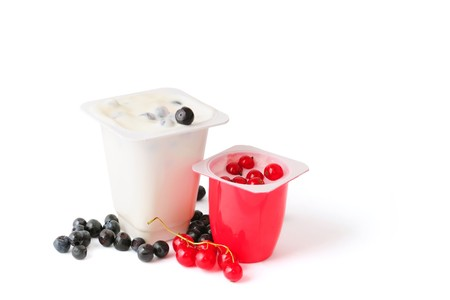 Two yoghurts with blueberries and red currants isolated on white photo