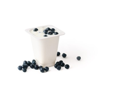 Yogurt in white plastic box with blueberries isolated photo