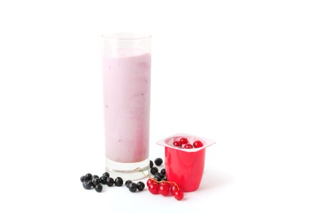 Berry yogurts in a glass and plastic package with blueberries and red currant photo