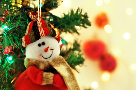 Cute smiling snowman toy on the Christmas tree with lights Stock Photo