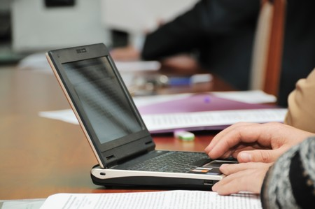 Business meeting or conference, focus on businessman�s hands on the netbook Stok Fotoğraf