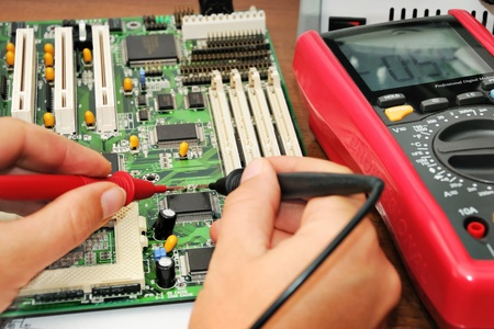 Technician in the lab testing a circuit board with multimeter Stock Photo