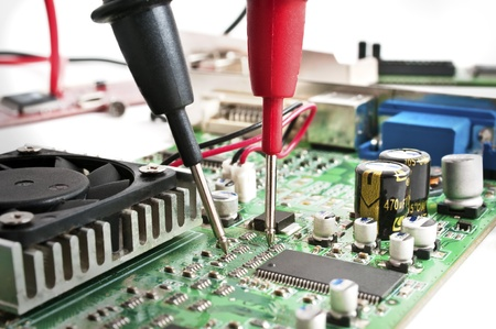 Multimeter probes examining a computer circuit board Stock Photo - 8679475