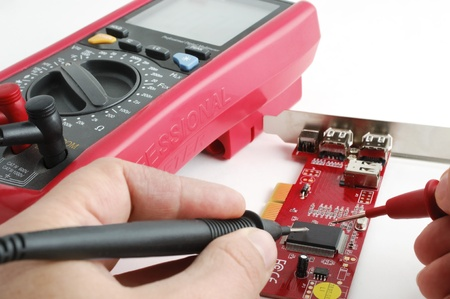 Computertechnicus onderzoekt een printplaat door een professionele multimeter