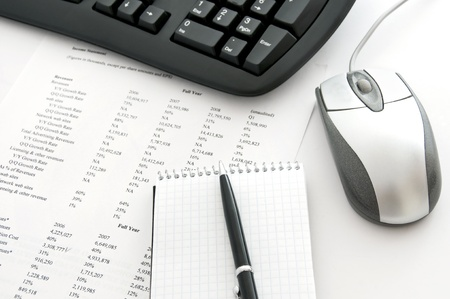 Blank notepad with pen, computer keyboard and mouse, sheet of paper with financial data photo