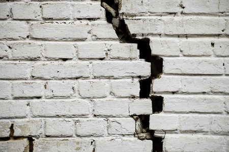 Artistic grunge background with old brick wall with a big crack