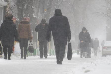Kiev, Oekraïne � februari 2011: mensen op straat lopen tijdens een sterke sneeuwval en koude wind.  Stockfoto
