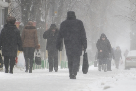 snowfall: KYIV, UKRAINE � FEBRUARY 2011: People walking on the street during a strong snowfall and cold wind.  Stock Photo