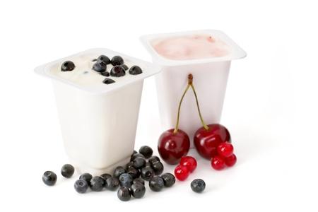 Twee yoghurt in plastic containers en bessen geïsoleerd op witte achtergrond Stockfoto