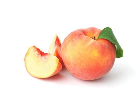 Ripe peach with green leaf and two cut sections isolated on white background