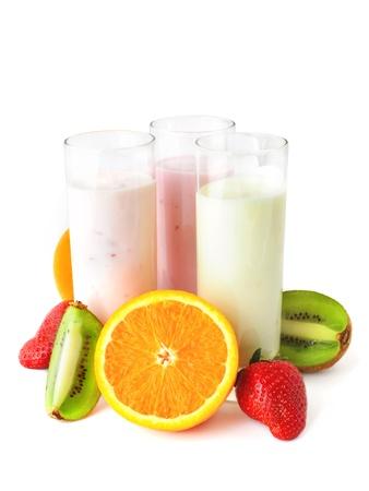Drie glazen met yoghurt omgeven door vers fruit. Gezond eten. Stockfoto