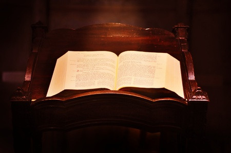 baptist: Opened old Bible with light beam galling on it in the church