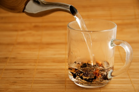 boiling: Boiling water pouring from the kettle to a cup with mixed black and fruit tea Stock Photo