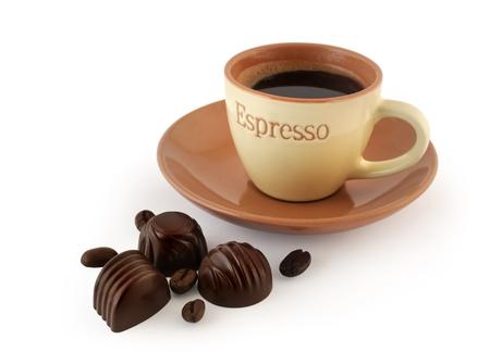 cafe bombon: Deliciosos dulces de chocolate suizo con café en grano y una taza de café sobre fondo blanco Foto de archivo