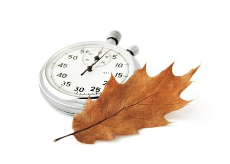 Chronometer and a dry oak leaf on white. Concept of passing time, can be used for autumn sales advertisement. Stock Photo