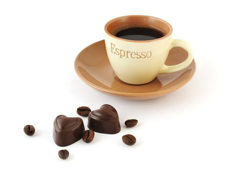 Heart-shaped chocolate candies, coffee-beans and a cup of espresso on white background Stock Photo - 13298357