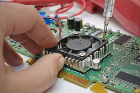 computer transistors: Electronic technician installs a cooler to a computer hardware