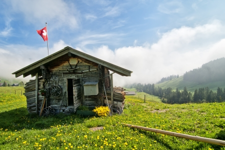 Traditional Swiss wooden hut with flag in the mountains
