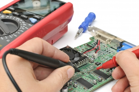 Close-up of a technician's hands with multimeter probes repairing a pc board