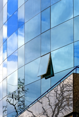 Modern business building with reflection of sky with clouds and trees photo