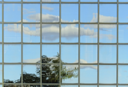 Glass wall of a corporate building with sky reflection photo