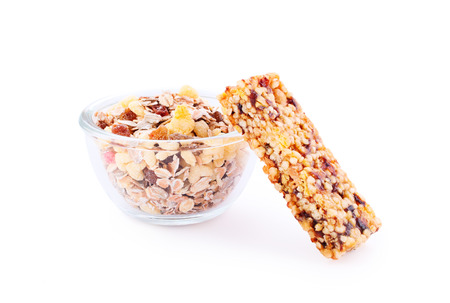 Muesli in a bowl and cereal bar isolated on white with shadow
