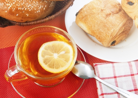 Cup of tea with lemon and sweet bakery on the table photo