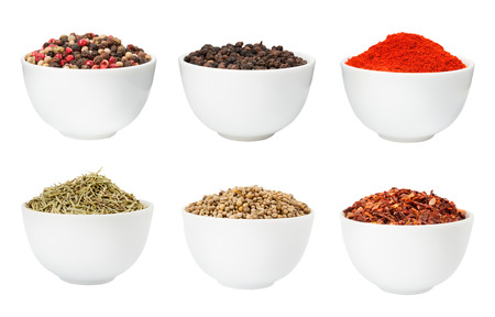 dried herbs: Pepper, rosemary, coriander and paprika spices in a bowls isolated on white