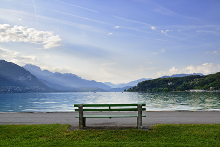 Place for rest with bench on a lawn near beautiful mountain lake Annecy Stok Fotoğraf