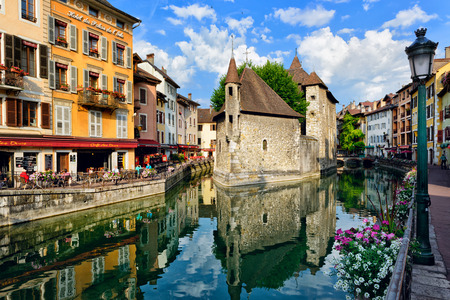 encircling: ANNECY, FRANCE - JUNE 22: People drink coffee near the River Thiou in Old Town, encircling the medieval palace perched mid-river - the Palais de lIsle on June 22, 2014 in Annecy, France.
