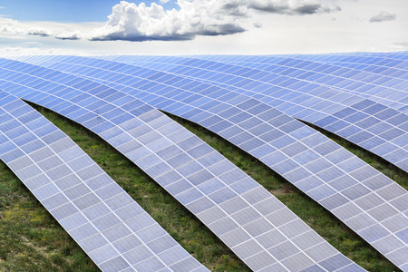 industry moody: Lines of solar panels against cloudy sky Stock Photo