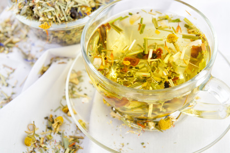 Herbal tea in the glass cup on a table with white tablecloth photo