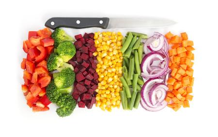 Snijd kleurrijke groenten in lijn met mes op een witte achtergrond Stockfoto