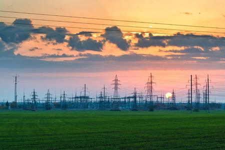 torres el�ctricas: Pilones central el�ctrica y los cables al atardecer Foto de archivo