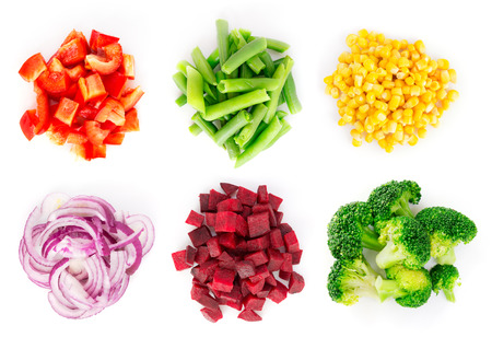 top: Heaps of different cut vegetables isolated on white background. Top view.