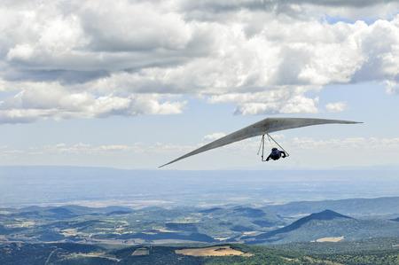 AGER, ESPAÑA 08 de agosto 2013: piloto no identificado volando bajo las nubes durante británica abiertos Concursos hanggliding. Foto de archivo