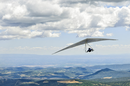 gliding: AGER, SPAIN – AUGUST 8, 2013: unidentified pilot soaring under the clouds during British Open hanggliding competitions. Stock Photo