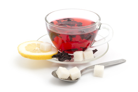 Hibiscus tea in the glass cup with lemon and sugar cubes on white background photo