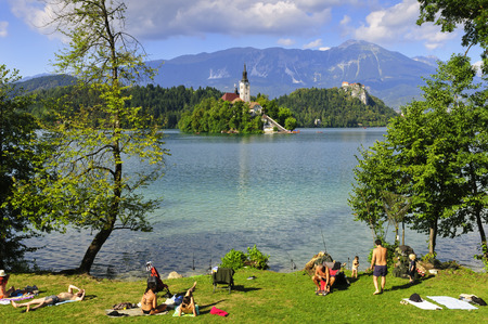 bled: BLED, SLOVENIA – AUGUST 15, 2013: people having rest near the famous Bled lake with amazing view on the island with historic monastery Editorial