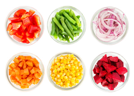 Assortment of cut vegetables in glass bowls isolated on white background. Top view.